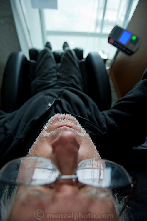 Seoul, Korea International Airport. Peter Menzel in massage chair. Self portrait. MODEL RELEASED.