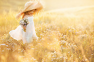Little girl with a bouquet of wild flowers in the meadow sunny summer day