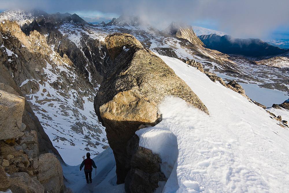 Climber Grace Marx descends through a narrow notch in the ridge below Dragontail Peak, Alpine Lakes Wilderness, Washington.
