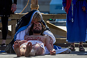 The final scenes of a dead Jesus being held by Mary after being lowered from the cross at the base of Nelsons Column during The Passion of Jesus which is performed in Londons Trafalgar Square by members of Wintershall Trust on London, 25th March 2016: Played annually on Good Friday it celebrates the cruxifixion and resurrection of Jesus Christ. The cast re-enacts the Christian Biblical story to an audience of thousands and the main character is played by professional actor James Burke-Dunsmore. .