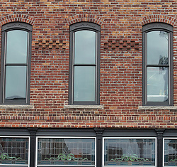 Brick building facade with detail work and arch topped windows and stained glass