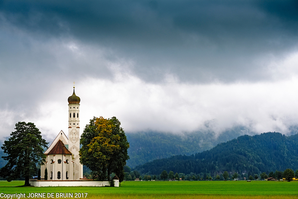 White church under a dark sky in front of the Bavarian Alps