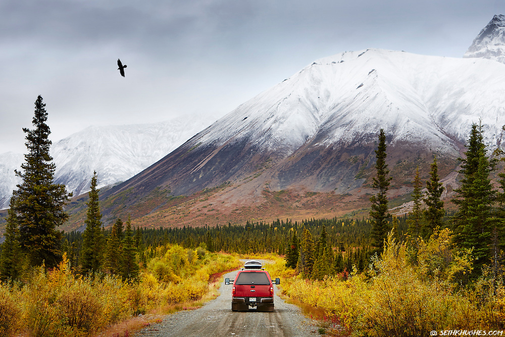 A red truck enters Wrangell-St. Elias National Park, Nabesna, Alaska with snow dusted mountains and autumn foliage covering the landscape.