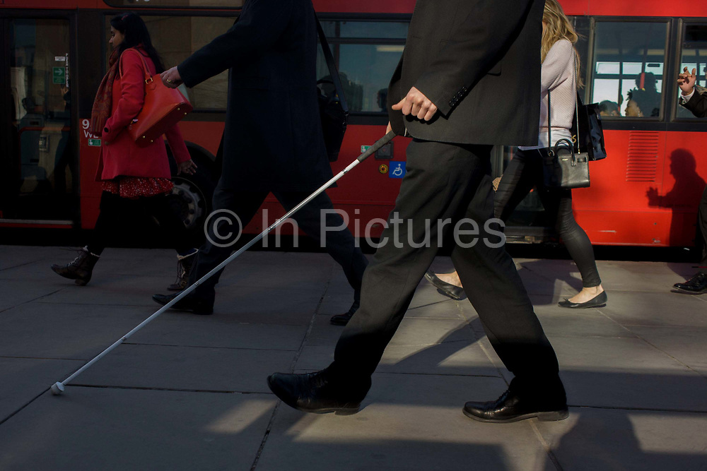 Unsighted or partially-sighted pedestrian crosses London Bridge during the evening rush hour. Using his stick to feel his way through the crowds and listening to the sounds of the city, he walks along surrounded by others on the pavement and in a passing bus. Commuters stride alongside a bus followed by others walking out of the City of London. There has been a crossing over the Thames here since the Romans first forded the river in the early 1st Century with subsequent medieval and Victorian stone bridges becoming an important thoroughfare from the City on the north bank, to Southwark on the south where transport hubs such as the mainline station gets commuters to the suburbs and satellite towns.