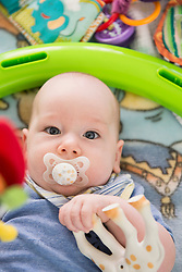 Close-up of baby with pacifier in mouth playing with a toy, Bavaria, Germany
