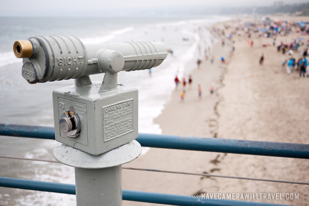 A coin operated telescope on Santa Monica pier overlooking the crowds of people on the beach and surf of Santa Monica. The shot has a very narrow field of focus on the telescope with the beach and people blurred out.