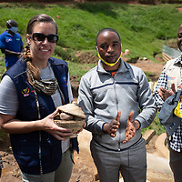 Meg Densmore is presented with a symbolic gift of potatoes by Lucien Mumbere Kangatsurwa during an event to mark the opening of a small reservoir near Butembo, Congo. The Reservoir was part of an IMA and Tearfund project to support communities and strengthen basic health care during the Ebola crisis which ended in June 2020.