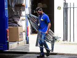 © Licensed to London News Pictures. 16/07/2016. London, UK. An ironing board and clothes horse being taken to a van marked fro David Cameron. Removal men begin to take items from numbers 10 and 11 at Downing Street at the end of the week that saw Prime Minister David Cameron leave and Theresa May arrive. Photo credit: Ben Cawthra/LNP