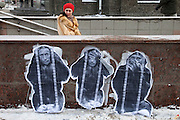 """Moscow, Russia, 04/02/2012..A woman enters a subway behind graffiti depicting Prime Minister Vladimir Putin as the three monkeys """"Hear no evil, see no evil, speak no evil"""" watches as tens of thousands of demonstrators march in central Moscow and protest against election fraud and Prime Minister Vladimir Putin in temperatures of -20 centigrade. Organisers claimed an attendance of 130,000 despite the bitter cold."""