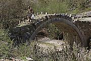 Greece, Epirus, Zagori, Pindus Mountains, Man walking across an old disused Arched Stone Bridge