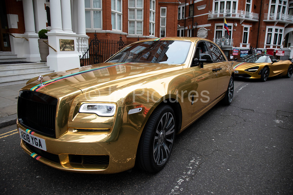 Gold Bentley and McLaren in the wealthy area of Knightbridge in London, United Kingdom. This is an area where the rich in their supercars parade them around driving with little more reason than showing off their exclisive cars.