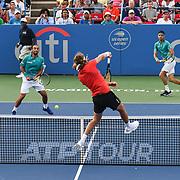 STEFANOS TSISPAS hits an overhead against  JUAN SEBASTION CABAL and ROBERT FARAH at the Rock Creek Tennis Center.