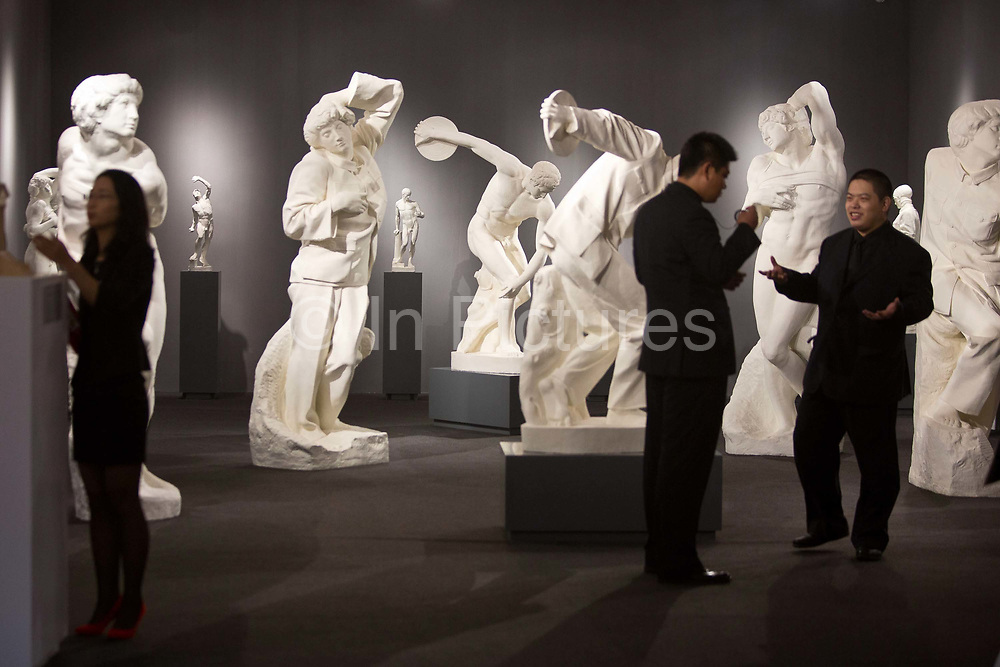 """Security guards stand amongst artworks during a public preview after a press conference announcing Christie's very first mainland China auction in Shanghai, China September 23,  2013. Both Southeby's and Christie's have opened an office in Mainland China in the past year, however they face overwhelming odds as China's state-owned auction houses such as Poly and Jiamu enjoys a near monopoly over China's art procurement market as foreigners are not allowed to buy vaguely defined """"historical"""" art."""