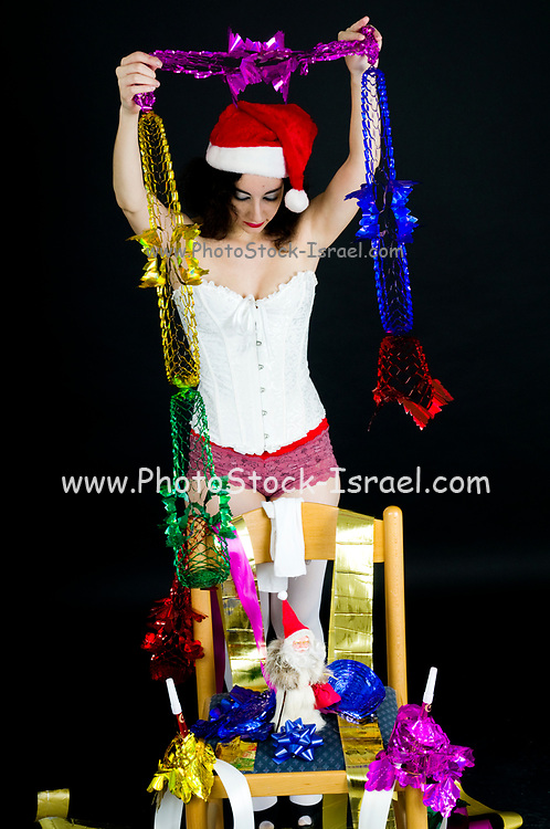 Young sexy woman in white corset wearing Santa hat prepares the Christmas decorations