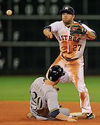 Jun 19, 2013; Houston, TX, USA; Houston Astros second baseman Jose Altuve (27) turns a double play as Milwaukee Brewers catcher Jonathan Lucroy (20) slides during the seventh inning at Minute Maid Park. Mandatory Credit: Thomas Campbell-USA TODAY Sports