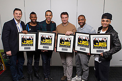 © Licensed to London News Pictures. 18/11/2013. London, UK. Pop group JLS are presented with an award for becoming the biggest selling boy band at The O2 arena after headlining a record 12 concerts at the London venue.  The band - left to right Oritse Williams, Marvin Humes, JB Gill and Aston Merrygold - are pictured backstage with Rob Snape of The O2 (far left) and tour promoter Simon Moran (middle), owner of SJM Concerts, ahead of their very last show after announcing their split earlier this year. Photo credit : David Fearn/LNP