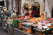 A man in a mask (which is commonplace for people who are sick and have to be out in public) rides his bicycle past a fruit and vegetable market in Kodaira City, Japan. Material World Project. The Ukita family lives in a 1421 square foot wooden frame house in a suburb northwest of Tokyo called Kodaira City.