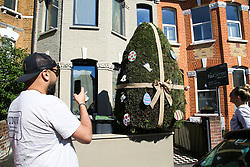 © Licensed to London News Pictures. 05/04/2020. London, UK. A man takes a photograph of a hedge in the front garden of a house in Haringey, north London which is decorated as an Easter Egg. Photo credit: Dinendra Haria/LNP