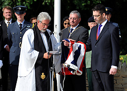 © licensed to London News Pictures. CARTERTON, UK.  01/09/11. The Chaplain of The Royal British Legion who is also the Vicar of Carterton and Brize Norton, The Rev Bill Blakey blesses the flag held by The Chairman of Brize Norton Parish Council Cllr Keith Glazier  and the Deputy Mayor of Carterton Cllr Adrian Coomber. A ceremony, attended by British Prime Minister David Cameron,  takes place at The Memorial Garden at Norton Way in Carterton, Oxfordshire today (01 Sept 2011). The Garden will become the focal point during the repatriation of UK service personnel from RAF Brize Norton. The Union Flag that used to fly at repatriations in Wooton Bassett was handed over and was blessed. . Mandatory Credit Stephen Simpson/LNP