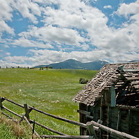 Fair weather cumulus clouds drift over a decaying barn in Montana's Gallatin Valley, near Bozeman. Mount Ellis and the southern Gallatin Range rise in the background.