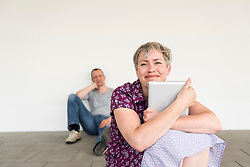 Mature woman holding digital tablet while mature man sitting in background