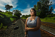 MARK DIORIO / Observer-Dispatch    Crystal Bollinger, 27, a resident counselor at the Rescue Mission and client advocate at the Carenet Pregnancy Center stands at the railroad tracks in West Utica where she tried to commit suicide in 2012. Bollinger now works to help individuals struggling with substance dependency and depression.