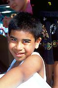 Boy age 7 smiling watching Cinco de Mayo parade.  St Paul  Minnesota USA