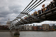 Supporters and protesters hold up their banners and placards on Millennium Bridge at the Rise For Climate Change event held outside Tate Modern in London, England, United Kingdom on September 8th 2018. Tens of thousands of people joined over 830 actions in 91 countries under the banner of Rise for Climate to demonstrate the urgency of the climate crisis. Communities around the world shined a spotlight on the increasing impacts they are experiencing and demanded local action to keep fossil fuels in the ground. There were hundreds of creative events and actions that challenged fossil fuels and called for a swift and just transition to 100% renewable energy for all. Event organizers emphasized community-led solutions, starting in places most impacted by pollution and climate change. Photographed for 350.org