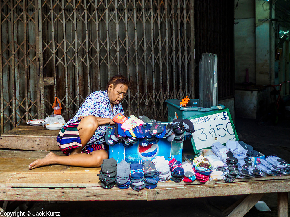28 MAY 2018 - BANGKOK, THAILAND: A woman sets up her stand to sell socks in Phra Khanong Market in Bangkok. The market serves a mix of Thai working class people and immigrants from Myanmar (Burma).      PHOTO BY JACK KURTZ