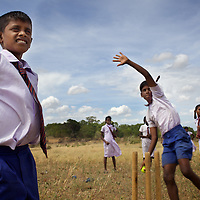 M. Chandrakumar, 11, plays cricket with other students at the Vadamunai Government Tamil Mixed School. <br /> <br /> Brothers M. Siranjeevithan, 13, and M. Chandrakumar, 11, attend Vadamunai Government Tamil Mixed School. Their father was killed, an innocent bystander in the conflict between the LTTE and Sri Lankan Government 11 years ago. The brothers' mother cares for them though they must both fish to supplement the family income. M. Siranjeevithan and M. Chandrakumar live with their mother in one of a dozen temporary makeshift shelters housing conflict-displaced Tamil families located 3km from the Vadamunai Government Tamil Mixed School.<br /> <br /> After fighting between the LTTE and Colombo Government forced displacement of the local Tamil community, the Vadamunai Government Tamil Mixed School was closed in 2007. Since reopening in January 2009, the school has six teaching staff for 88 pupils. Before closure, 136 pupils studied at the school. Five classes are held in a Unicef supplied Temporary Learning Space. Four other classes are conducted outside. Many of the students suffer with the trauma and stress associated with those living in conflict situations. The staff must deal with these issues as well as the personal difficulties that they also themselves suffer living in a conflict environment. <br /> <br /> Photo: Tom Pietrasik<br /> Batticaloa District, Sri Lanka<br /> September 30th 2009