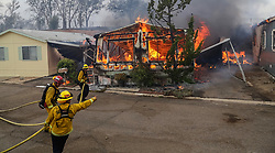 July 5, 2018 - San Diego, California, U.S. - Firefighters battle flames at the Alpine Oaks Estates mobile home park on Friday during a fire in Alpine, California. (Credit Image: © Eduardo Contreras/San Diego Union-Tribune via ZUMA Wire)