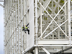 © Licensed to London News Pictures. 27/11/2012.. Two Absailers remove the final  piece of wrap from the exterior of the aquatic centre in the Olympic Park. to mark the hand over of the Olympic Park from LOCOG to the London Legacy Development Company.Photo credit : Andrew Baker/LNP