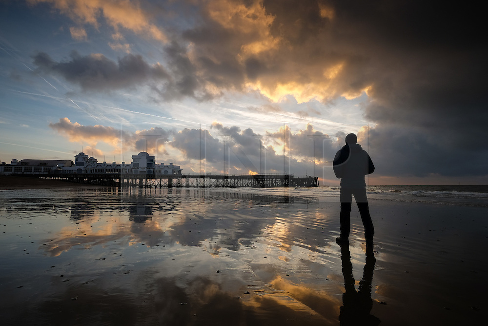 © Licensed to London News Pictures. 04/10/2016. Southsea, Hampshire, UK.  A man walks on the beach as dawn breaks over South Parade Pier in Southsea this morning, 4th October 2016. Today will be another dry and sunny, but breezy, autumn day in the south of England. Photo credit: Rob Arnold/LNP