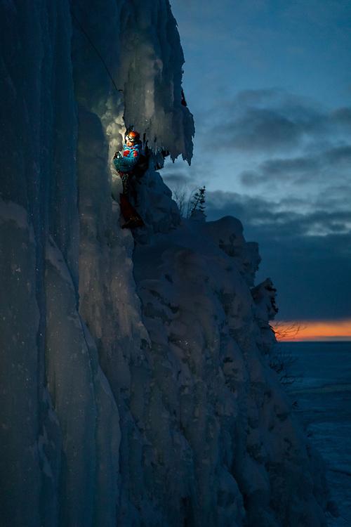 Etienne Rancourt climbing Meduse, WI4 in Gaspesie, Quebec at dusk