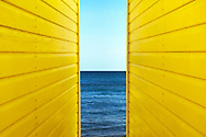 Symetrical perspective of 2 Yellow Beach Huts with blue sky and sea inbetween them.