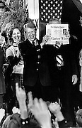 """President elect Jimmy Carter holds a newspaper with the headline """"Carter Wins!"""" as he celebrates with crowds filling the streets of tiny Plains, Georgia on election night in 1976. - To license this image, click on the shopping cart below -"""