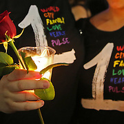 Mourners are seen during a vigil at the Dr. Phillips Center for the Performing Arts for the victims of a mass shooting at the Pulse nightclub Monday, June 13, 2016, in Orlando, Florida.  A gunman killed dozens of people in a massacre at the crowded gay nightclub in Orlando on Sunday, making it the deadliest mass shooting in modern U.S. history. (Alex Menendez via AP)