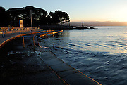 View of Opatija in early morning light, looking toward Lady With Seagull statue, with concrete ocean-front and steps in foreground. Opatija, Croatia