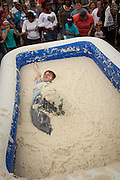 A competitor rolls around in a pool of instant grits during the grits roll competition at the World Grits Festival April 14, 2012 in St. George, SC. The festival celebrates the southern love for the sticky corn porridge