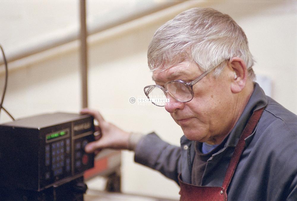 Man programming plasma cutting machine at engineering works,