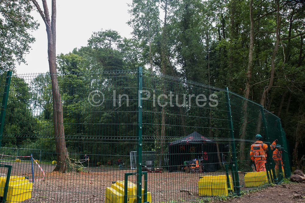 HS2 security guards monitor a compound established to facilitate tree felling in Denham Country Park on 13th July 2020 in Denham, United Kingdom. The HS2 project is currently projected to cost around £106bn and will remain a net contributor to CO2 emissions during its projected 120-year lifetime.