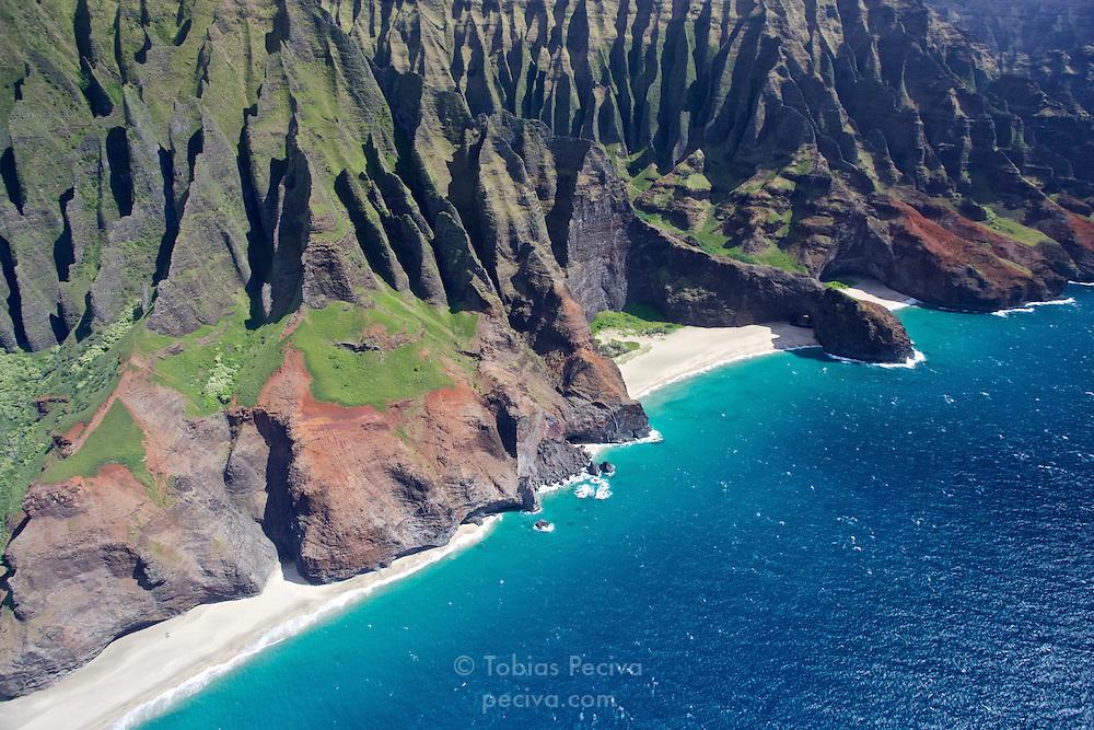 Sheer cliffs and sharp ridges back deserted beaches along the Na Pali coastline, on Kauai, Hawaii.