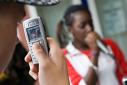 Teenager taking a photograph on mobile phone of singer performing during a community day promoting learning and diversity,