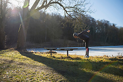 Young man doing stretching on fitness trail by frozen lake