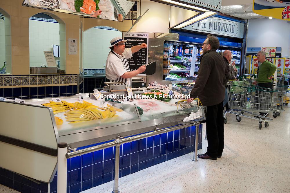 A fish monger serves a customer at Morrisons Supermarket, UK.