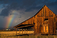Rainbow and storm clouds at sunrise over old wooden barn, near Susanville, Lassen County, California