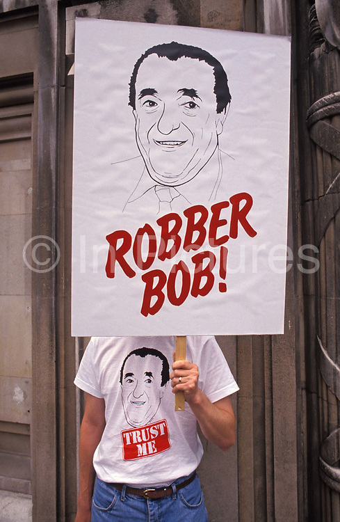 A protester wearing a Robert Maxwell t-shirt stands outside the entrance of Mirror Group Newspapers at a time when its pension fund was found to have been stolen by its tycoon owner, Robert Maxwell from former employees, on 9th June 1992, in London, England.