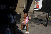 Girl in stripes passes-by railings and child theme advertisement in south London.