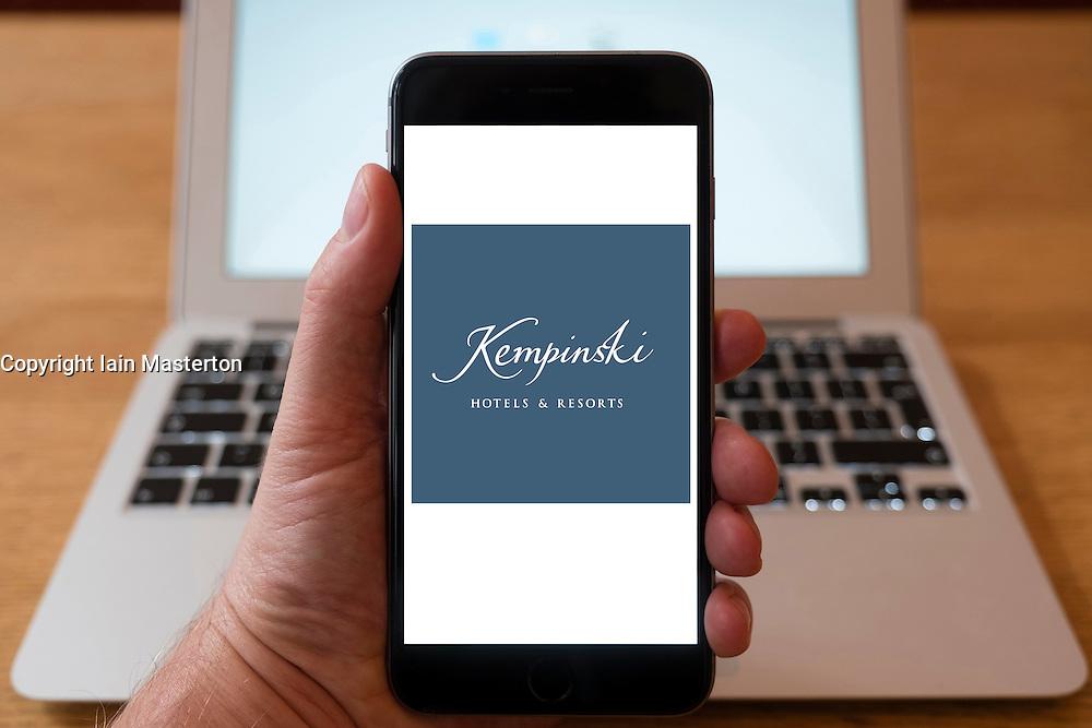 Using iPhone smartphone to display logo of Kempinski luxury hotels group