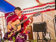 "14 JULY 2012 - FT DEFIANCE, AZ:   ANDREW MCCLELLAN, 10, sings a hymn during the ""Singspiration"" a gospel jam/prayer meeting at the 23rd annual Navajo Nation Camp Meeting in Ft. Defiance, north of Window Rock, AZ, on the Navajo reservation. Preachers from across the Navajo Nation, and the western US, come to Navajo Nation Camp Meeting to preach an evangelical form of Christianity. Evangelical Christians make up a growing part of the reservation - there are now more than a hundred camp meetings and tent revivals on the reservation every year. The camp meeting in Ft. Defiance draws nearly 200 people each night of its six day run. Many of the attendees convert to evangelical Christianity from traditional Navajo beliefs, Catholicism or Mormonism. ""Camp meetings"" are a form of Protestant Christian religious services originating in Britain and once common in rural parts of the United States. People would travel a great distance to a particular site to camp out, listen to itinerant preachers, and pray. This suited the rural life, before cars and highways were common, because rural areas often lacked traditional churches.  PHOTO BY JACK KURTZ"